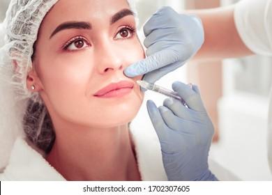 Into upper lip. Dark-eyed appealing client having injection into upper lip enjoying beauty treatment