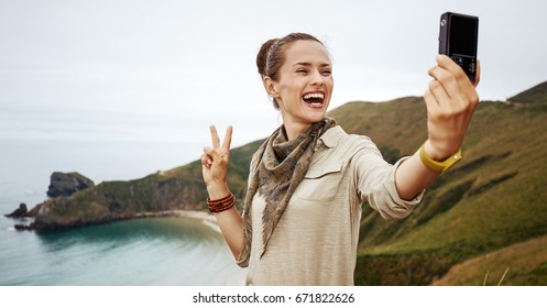 Into the wild in Spain. healthy woman hiker taking selfie with digital camera and showing victory in front of ocean view landscape