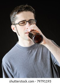 Intoxicated young man drinking out of a brown beer bottle.