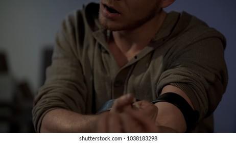 Intoxicated young man enjoying himself while injecting drug dose with syringe
