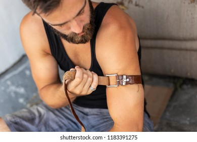 Intravenous junkey applying a belt as a tourniquet before shooting up with a heroin. Focus on the belt