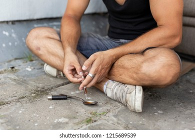 Intravenous junkie filling up a heroin syringe getting cooked heroin from a spoon, getting his shoot up dose ready. Focus on the syringe and the hands