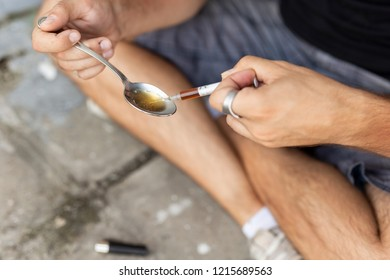 Intravenous junkie filling up a heroin syringe getting cooked heroin from a spoon, getting his shoot up dose ready. Focus on the needle and the spoon