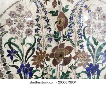 An intricate and beautiful inlay stone work. Close up of floral design pattern made with stone work in the wall.