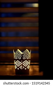 Intricate candle holder with lit candle at night. Selective focus.