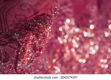 Intricate embroidery of beads and sequins on transparent red fabric.