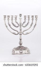 Intricate silver menorah on a white surface. Silver menorah isolated on white background.