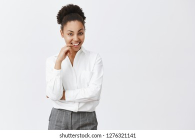 Intrigued coworker listenng dirty stories with smirk. Curious charming and playful african female in white shirt and pants, biting finger flirty and smiling while having interesting and daring idea