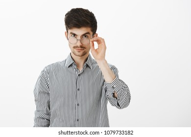 I am intrigued. Handsome confident young caucasian male coworker, looking from under forehead with lifted eyebrow, holding rim of glasses, being suspicious and interested in topic of conversation