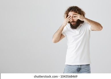Intrigued and interested mature eastern man with curly hair and beard covering eyes with palms and peeking through fingers, being curious what is happening, standing over gray background