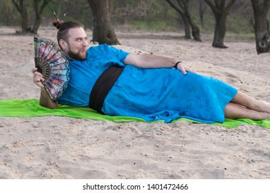 intrigued transsexual handsome man with make up, hair bun lying on sand in blue kimono, holding hand fan and looking at camera on rug