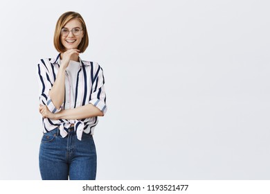 I am intrigued, wanna listen your idea. European stylish female teacher in trendy glasses, holding hand on chin in curious pose, smiling joyfully, interested in theory of colleague over grey wall