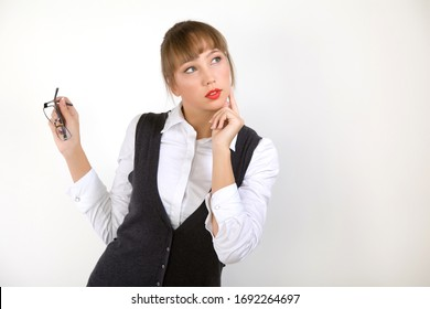 Intrigued young beautiful woman manager or secretary in formal clothes on a white background looks away on a white background. Concept of advertising and special offers and promotions