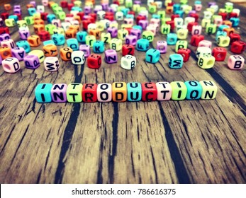 INTRODUCTION word of colourful cube alphabet on wooden table.