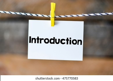 Introduction.Introduction on paper hanging on the clothesline. On old wood background