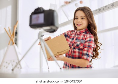 Introductory remarks. Pleasant cheerful pre-teen girl in a checked shirt holding a box in her hands and presenting it at the beginning in her unboxing video