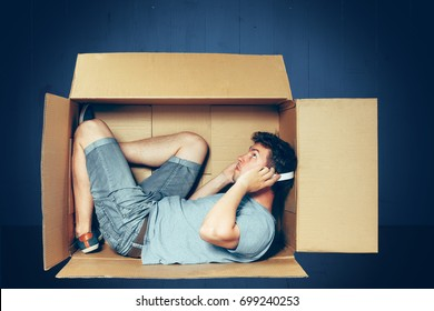 Introvert concept. The man sitting inside box and working with laptop