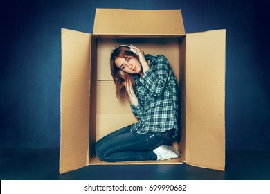 Introvert concept. Woman sitting inside box and with headphones