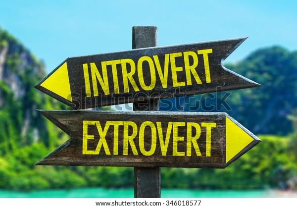 Introvert - Extrovert signpost in a beach background