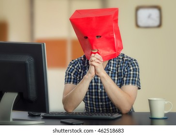 Introverted guy is frightened at first time on-line dating. Man wears checkered shirt and red paper bag over head. His hands are clenched in front of face. He sits at black desk and looks at monitor