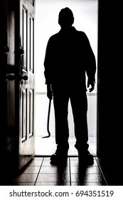 Intruder standing at doorway threshold, in silhouette with crowbar