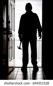 Intruder standing at doorway threshold, in silhouette with claw hammer