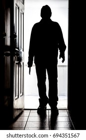 Intruder standing at doorway threshold, in silhouette with buck knife