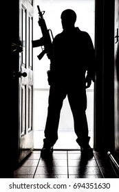 Intruder standing at doorway threshold, in silhouette with AR-15 style long gun