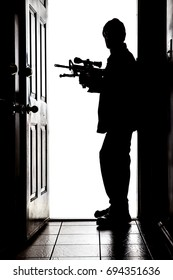 Intruder standing at doorway threshold, in silhouette with AR-15 rifle