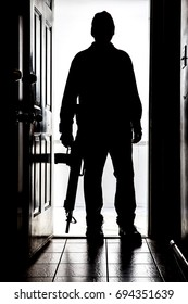 Intruder standing at doorway threshold, in silhouette with AR-15 style shotgun
