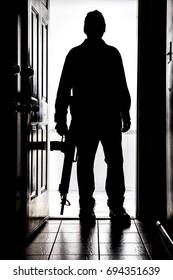 Intruder standing at doorway threshold, in silhouette with AR-15 style shotgun