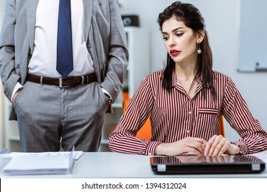 Intrusive strong boss. Flawless long-haired woman in striped blouse sitting on working place and her boss pressing on her