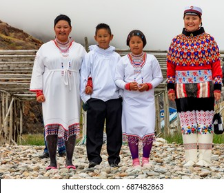 INUIT FAMILY IN TRADITIONAL CLOTHES WELCOMING TOURISTS IN NIOQORNAT, GREENLAND - AUGUST 2016