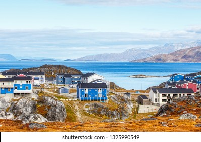 Inuit houses and cottages in residential district of Nuuk city with fjord and mountains in the background, Greenland