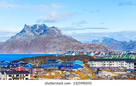 Inuit houses and cottages scattered across tundra landscape in residential suburb of Nuuk city with fjord and mountains in the background, Greenland