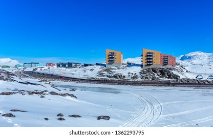 Inuit multistory houses of Nuuk city on the rocks with mountains in the background, Greenland