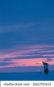 Inuit woman ice fishing in traditional clothing with an ivory kakivak fish spear amidst a beautiful sunset skyline