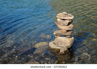 Inukshuk in the clear waters of Moraine Lake with ripples