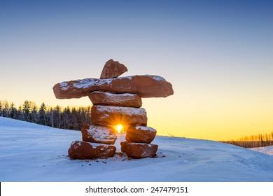 Inukshuk with dusting of snow at sunset