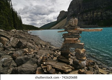 An Inukshuk - Inuit inspired rock statue - stands by a lake in Canada. The photo was taken in the Rocky Mountains in Alberta, but is suitable for a wide variety of uses.