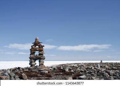 Inukshuk or Inuksuk landmark with frozen bay in the background near Arviat, Nunavut