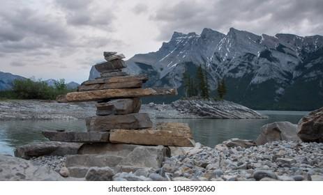 Inukshuk, landmark or Cairn on the shore of Lake Minewanka in Banff National Park, Alberta at sunrise