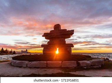 Inukshuk perfectly framing the setting sun in summer, Collingwood, Ontario