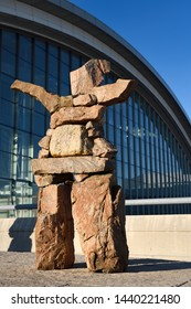 Inukshuk red stone statue with outstretched welcoming arms at Pearson International Airport Terminal 1 Toronto Canada in morning sunrise Toronto, Ontario, Canada - June 7, 2019