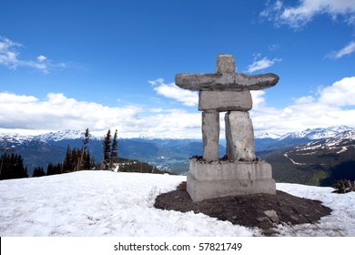 Inukshuk at the top of Whistler Peak in British Columbia, Canada, with snow, blue sky, white clouds and mountains in the distance