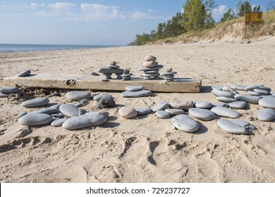 Inukshuks on a board on an empty sandy beach on a sunny day. Other flats rocks are scattered about.