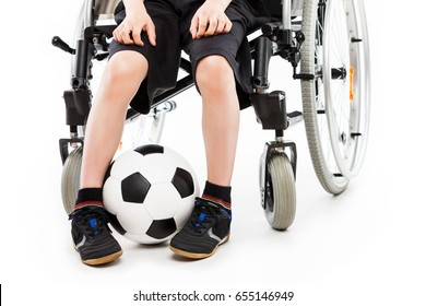 Invalid or disabled child boy sitting on wheelchair hand holding soccer sport ball white isolated