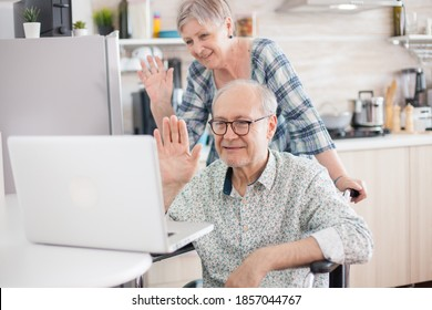 Invalid man and wife saying hello to their family. Disabled senior man in wheelchair and his wife having a video conference on laptop in kitchen. Paralyzed old man and his wife having a online