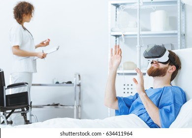 Invalid patient wearing virtual reality simulator in white hospital room