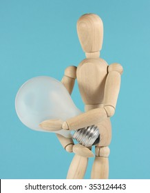 Inventor holds idea / light bulb in her arms, protects patent
